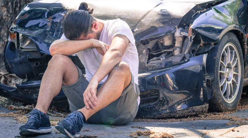 man sitting on the ground in front of his wrecked car head in his arms weeping, Psychological impact of fatal car accidents